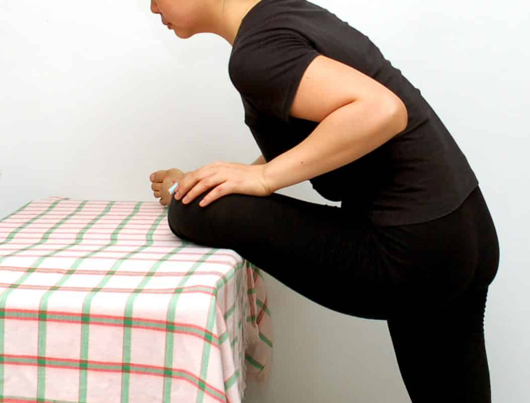 Lean forward at the hips and place your elbows on a table.